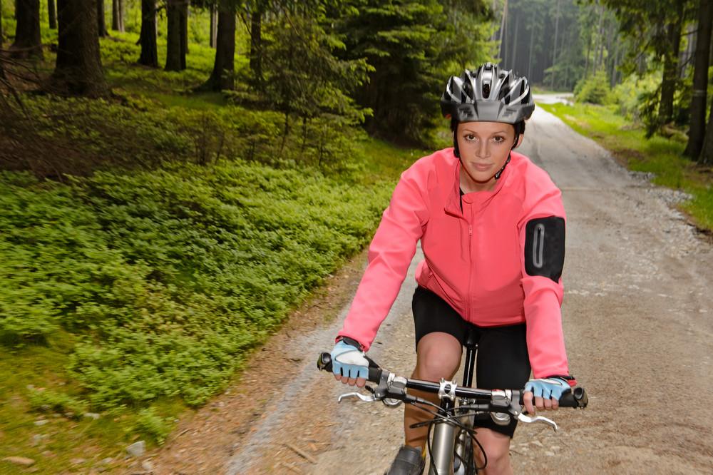 Woman mountain biking through forest road blur motion