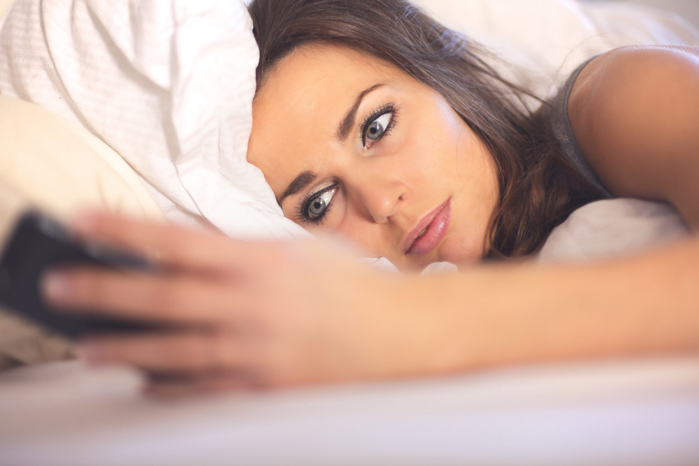 Woman on Bed Reading a Text Message
