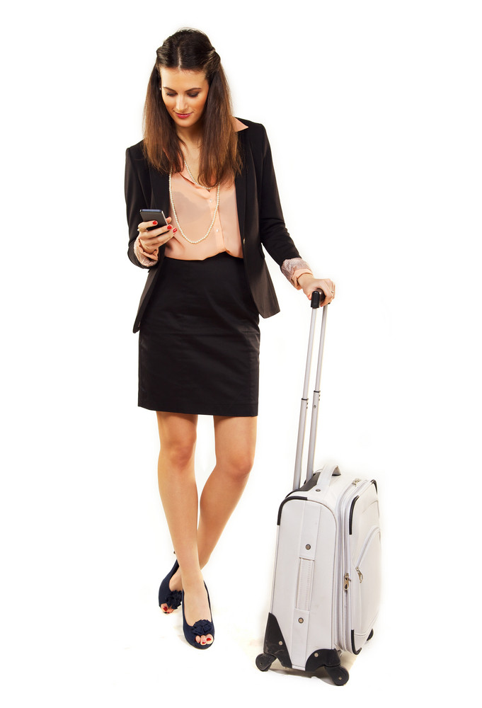 Woman on business trip reading text messages on her cellphone