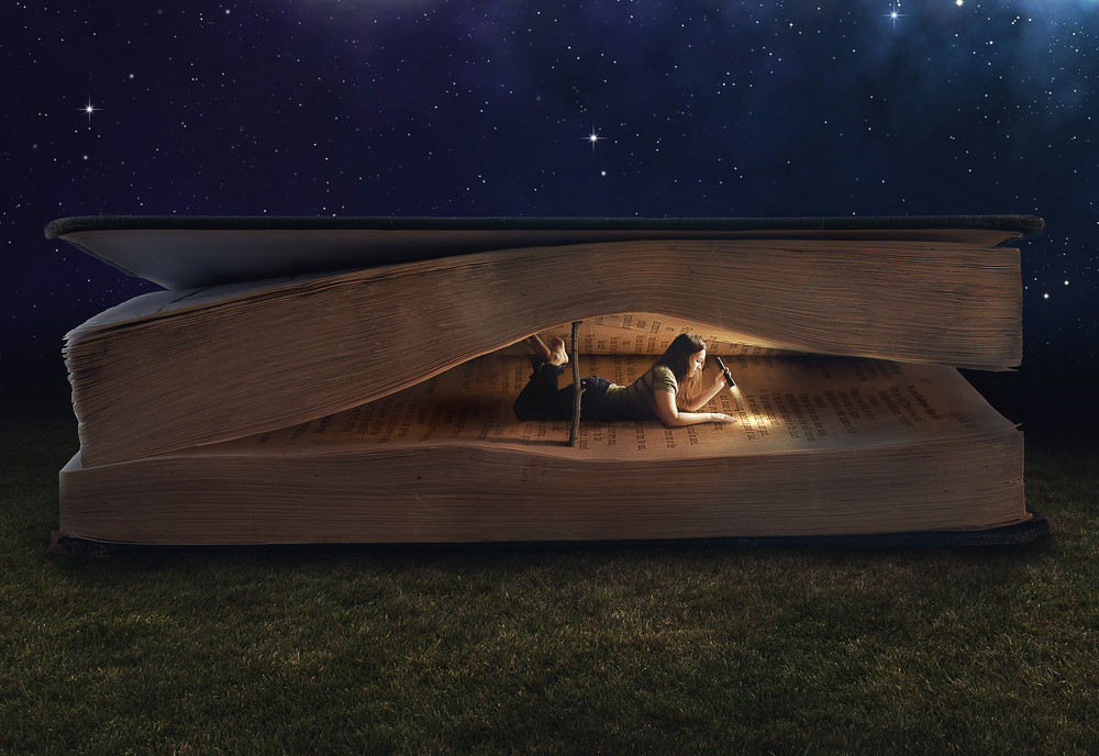 Woman reading inside a huge book at night.