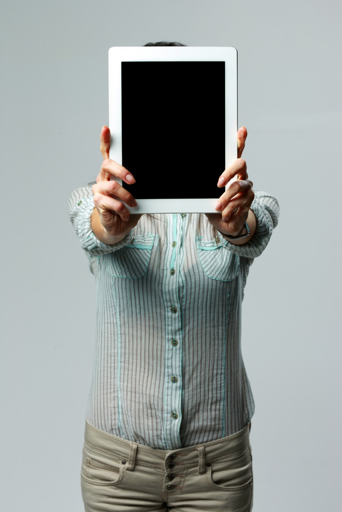 Woman showing tablet computer screen on gray background