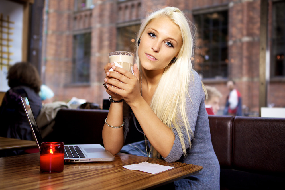 Woman sitting on a cafe with her laptop and drinking a cup of coffee.
