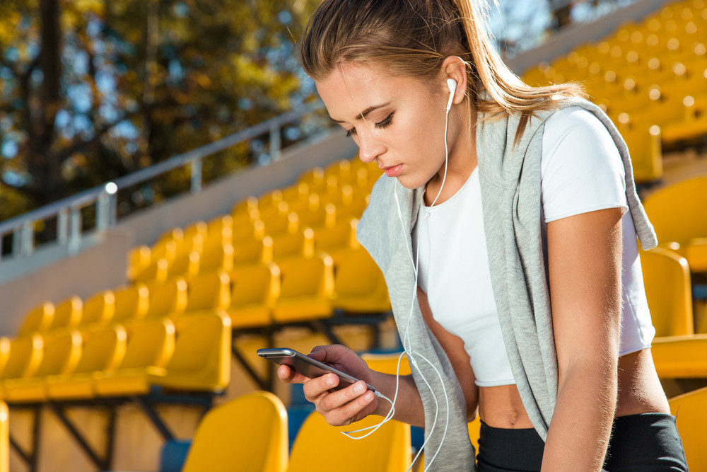 Woman using smartphone on stadium