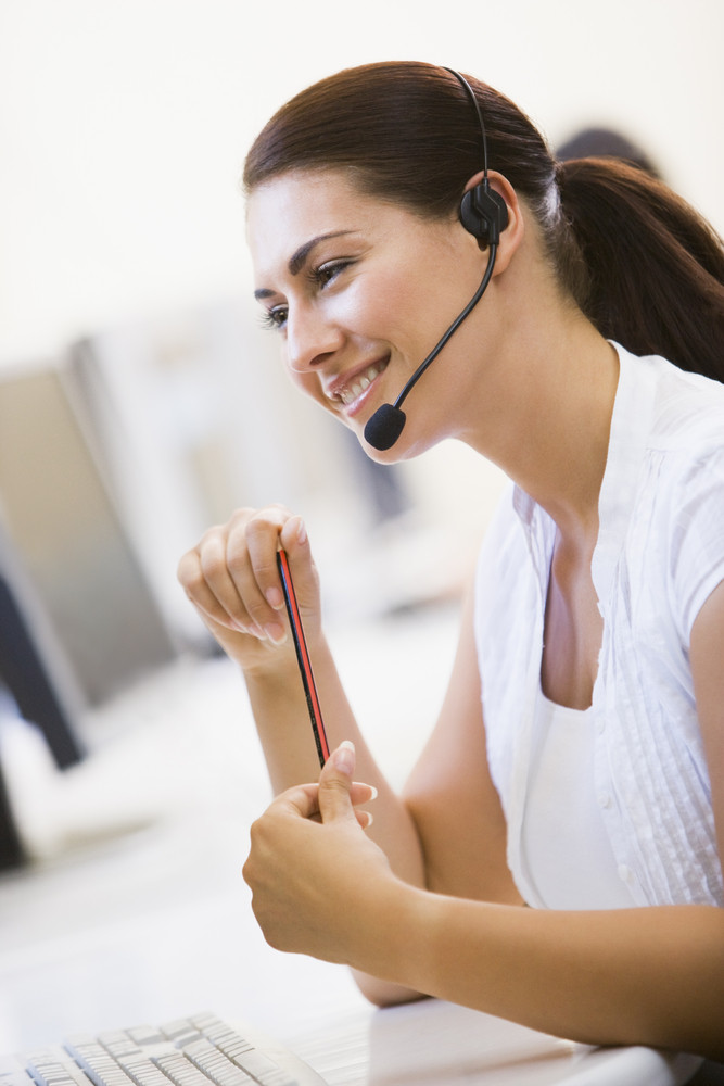 665269fc07d Woman wearing headset in computer room smiling Royalty-Free Stock ...