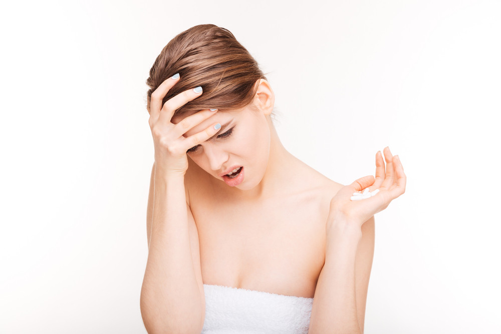 Woman with headache holding pills isolated on a white background