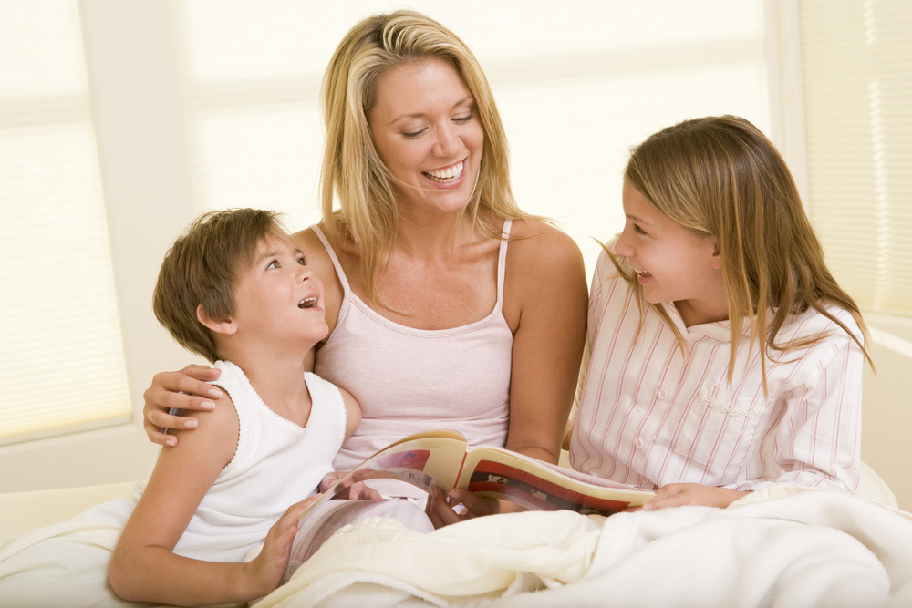 Woman with two young children sitting in bed reading book and smiling