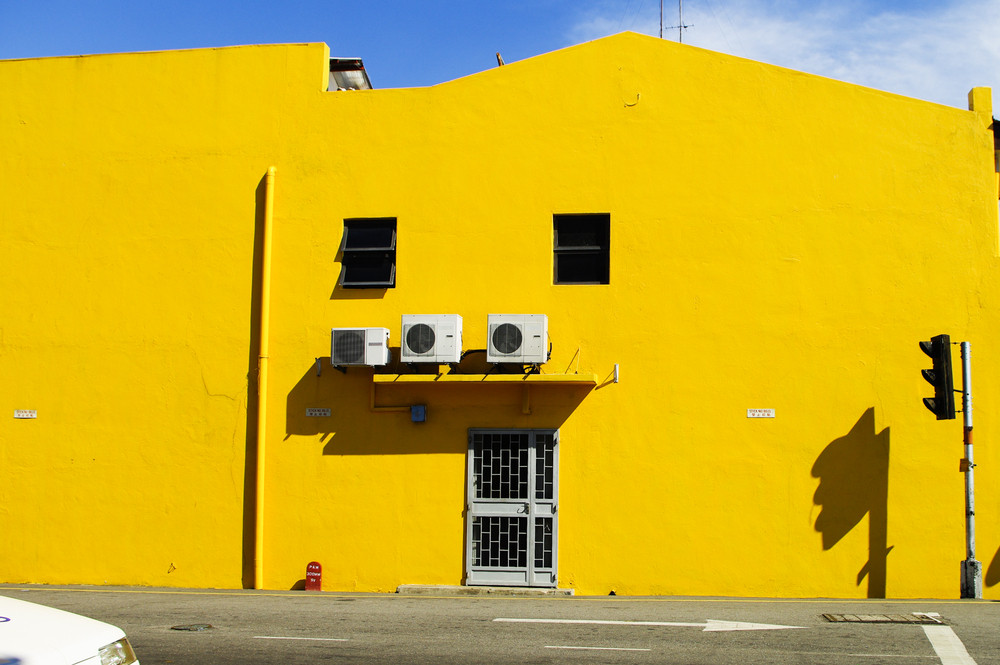 Yellow building wall with door and window on the road. Melaka. Malaysia