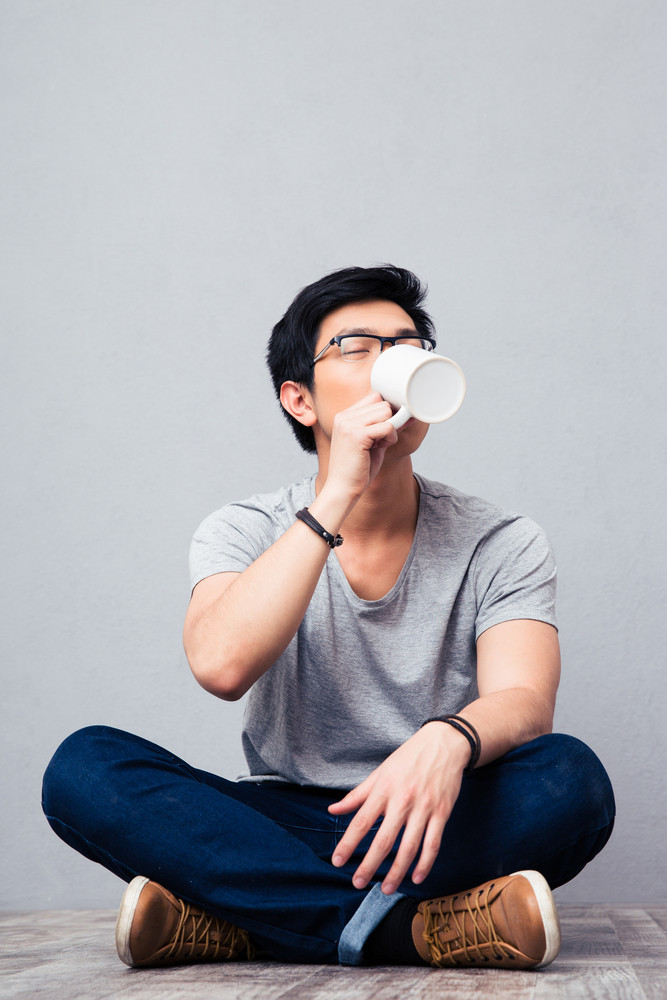 Young asian man drinking coffee