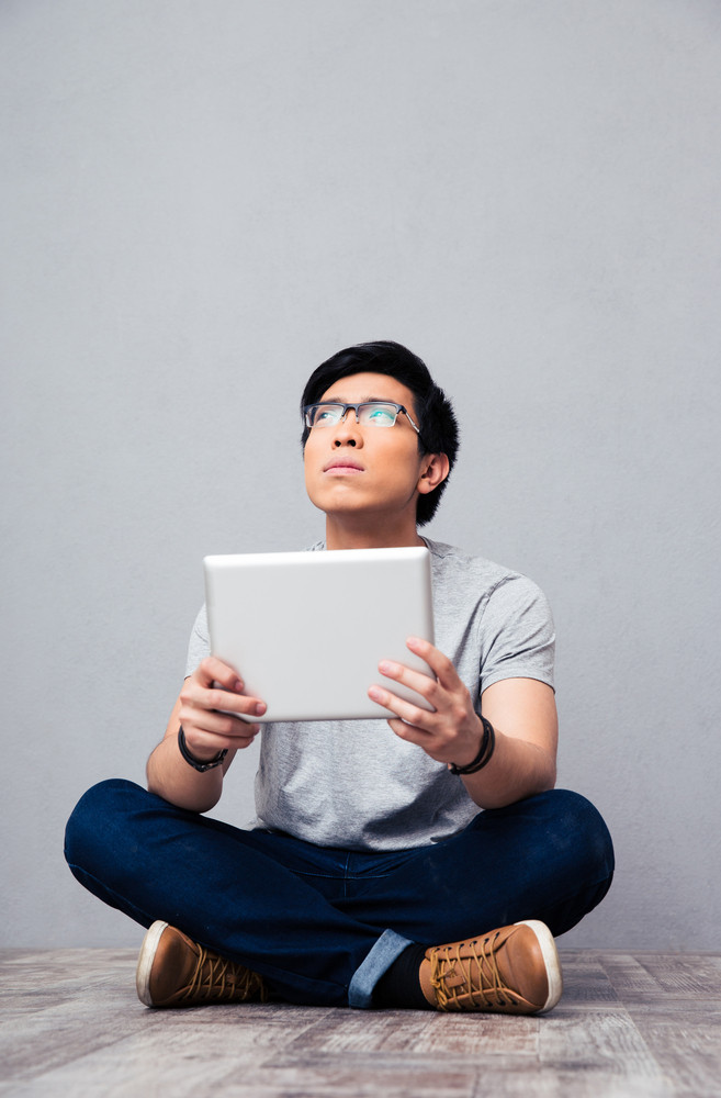 Young asian man holding tablet computer