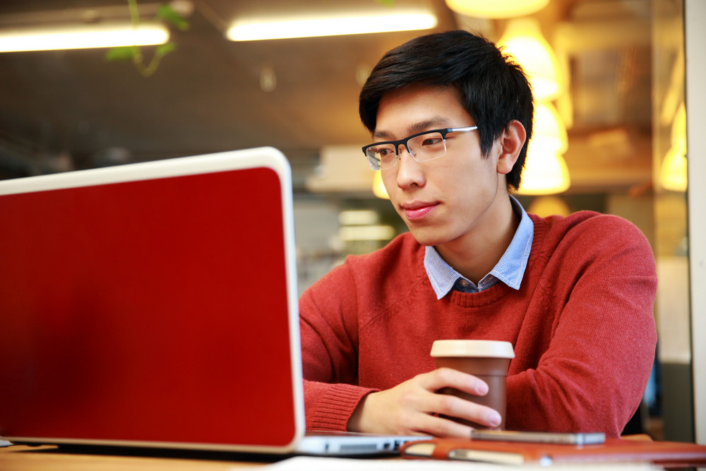 Young asian man in glasses working on laptop and holding cup of coffee