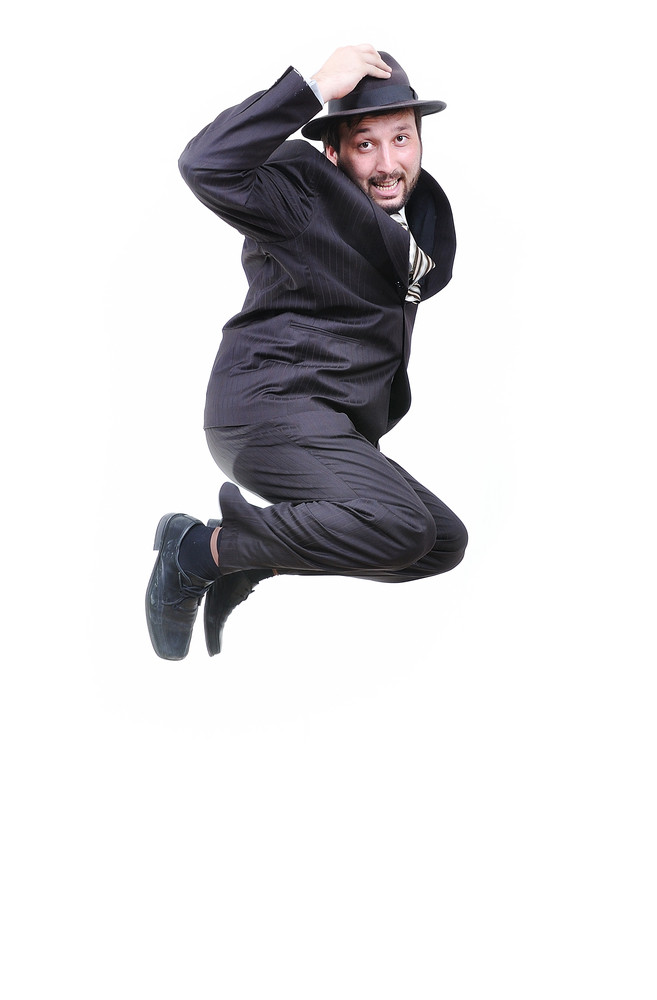 Young attractive businessman jumping with hat on head