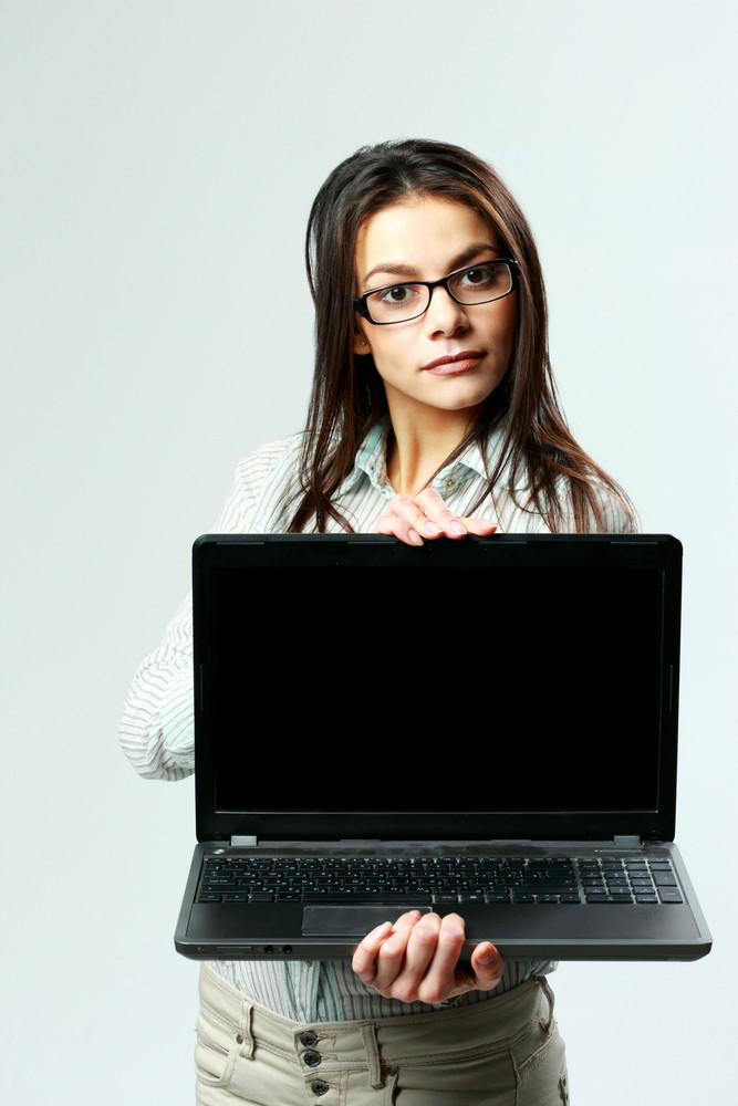 Young beautiful businesswoman showing laptop on gray background