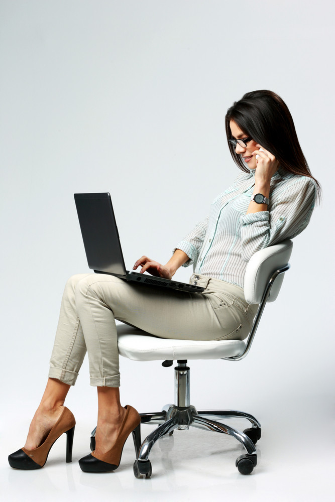 Young beautiful businesswoman using laptop and talking on the phone on gray background