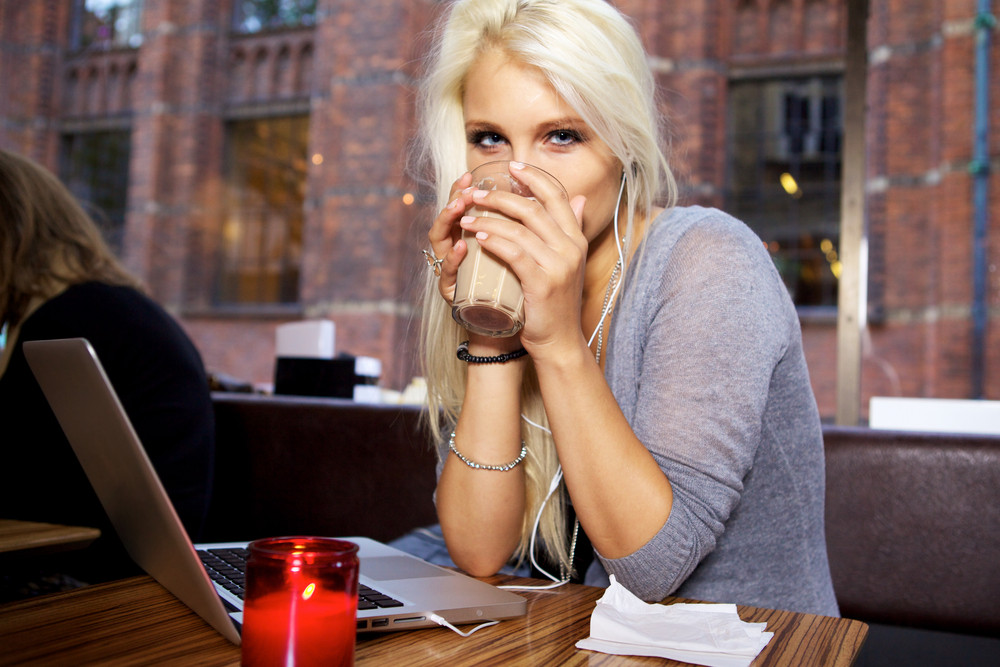 Young beautiful woman having a coffee break on a cafe.