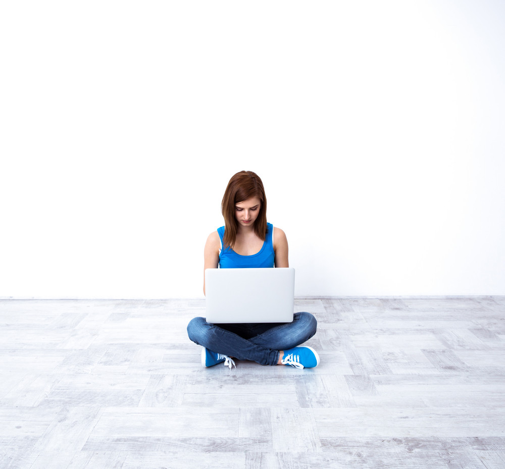 Young beautiful woman sitting at the floor and using laptop