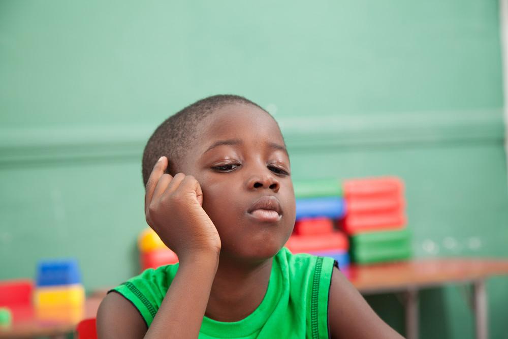 Young black boy thinking in kindergarten