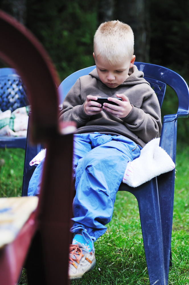 Young boy playing games on phone