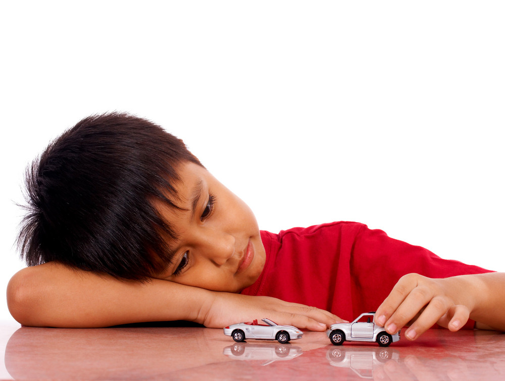 Young Boy Pushing His Cars On The Table