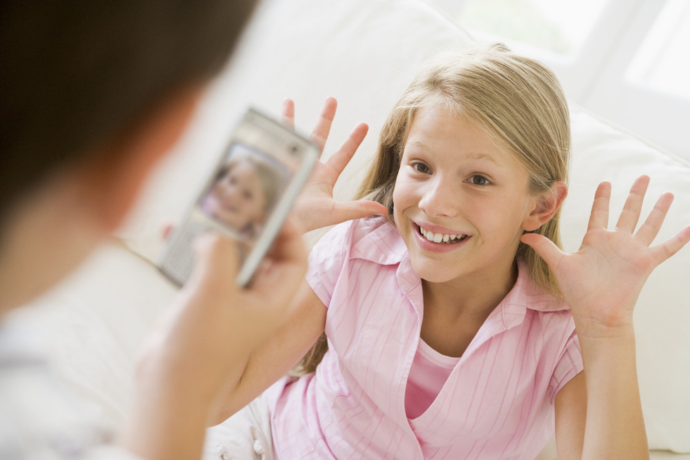 Young boy taking picture of smiling young girl with camera phone indoors