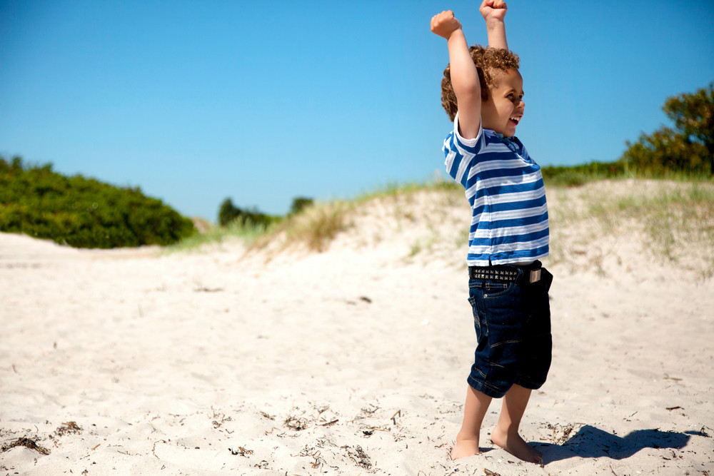 Young boy with arms stretched looks happy as he plays on the sand