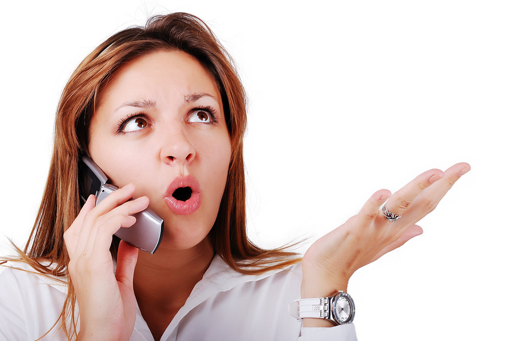 Young brunette with surprised expression on face speakin on cell phone