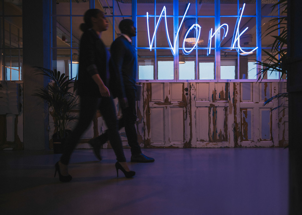 Young business people walking through office corridor with neon light work sign.