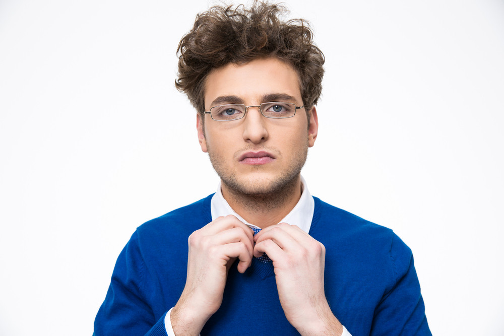 Young businessman in glasses straightens his tie