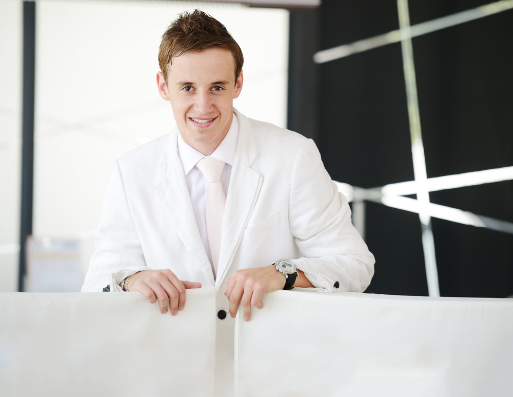 Young businessman standing in modern office lobby with copy space