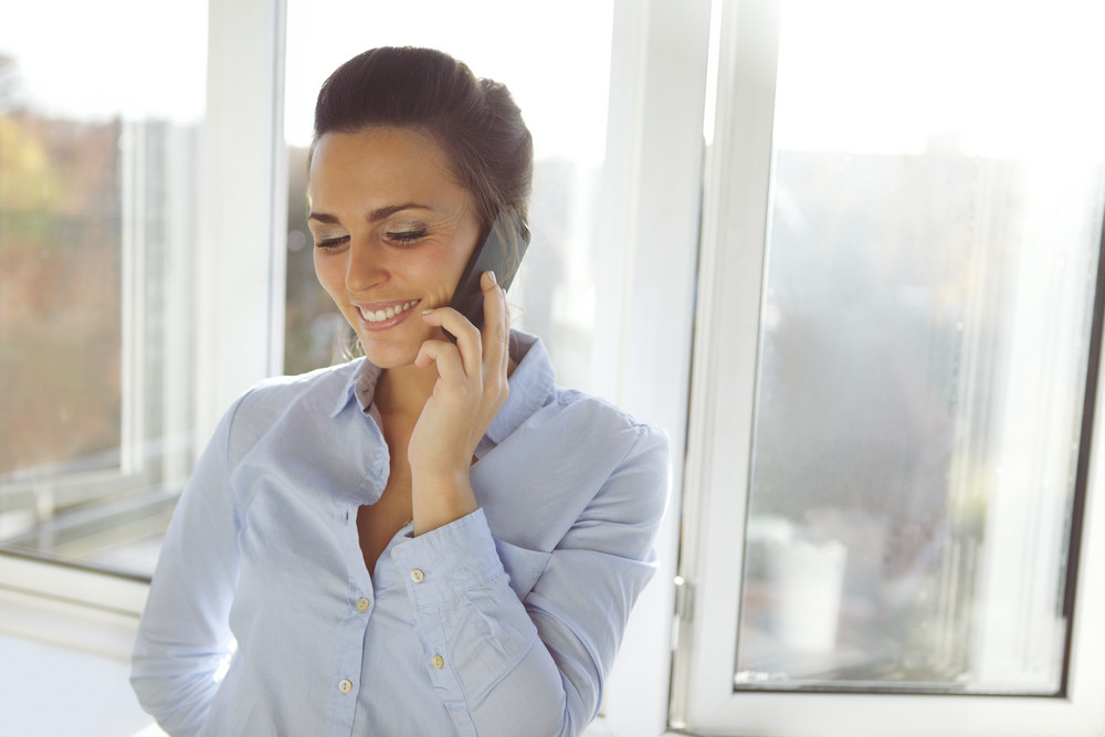 Young businesswoman in conversation on cell phone while standing by window in office. Beautiful young female model in formal wear.