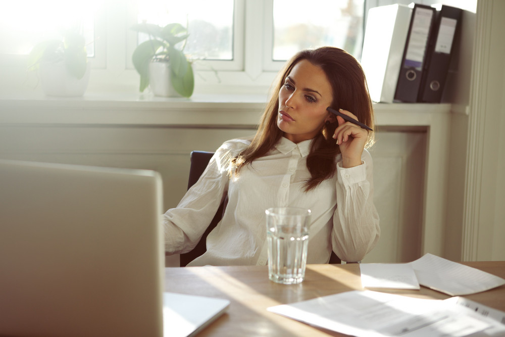 Young businesswoman looking at laptop and thinking. Beautiful young woman working from home. Caucasian female in home office.