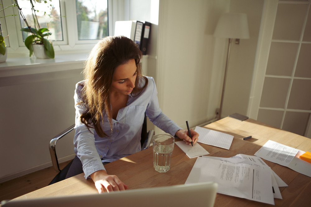 Young businesswoman sitting at her desk writing notes from a laptop at home. Beautiful caucasian female working from home office.