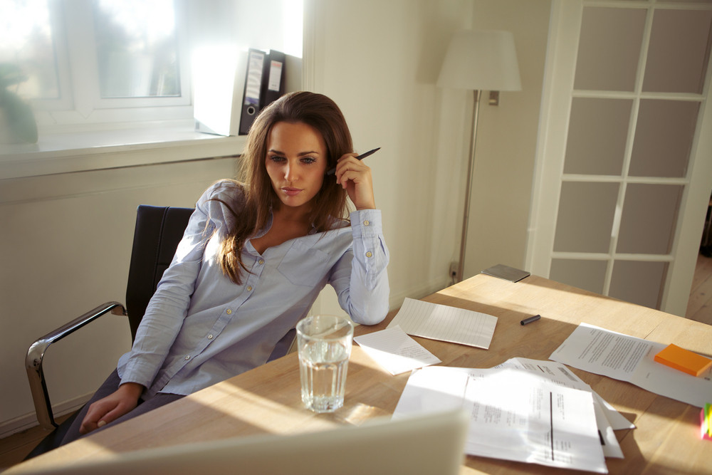 Young businesswoman thinking about the new business plan. Beautiful young woman sitting at her desk with laptop working from home.
