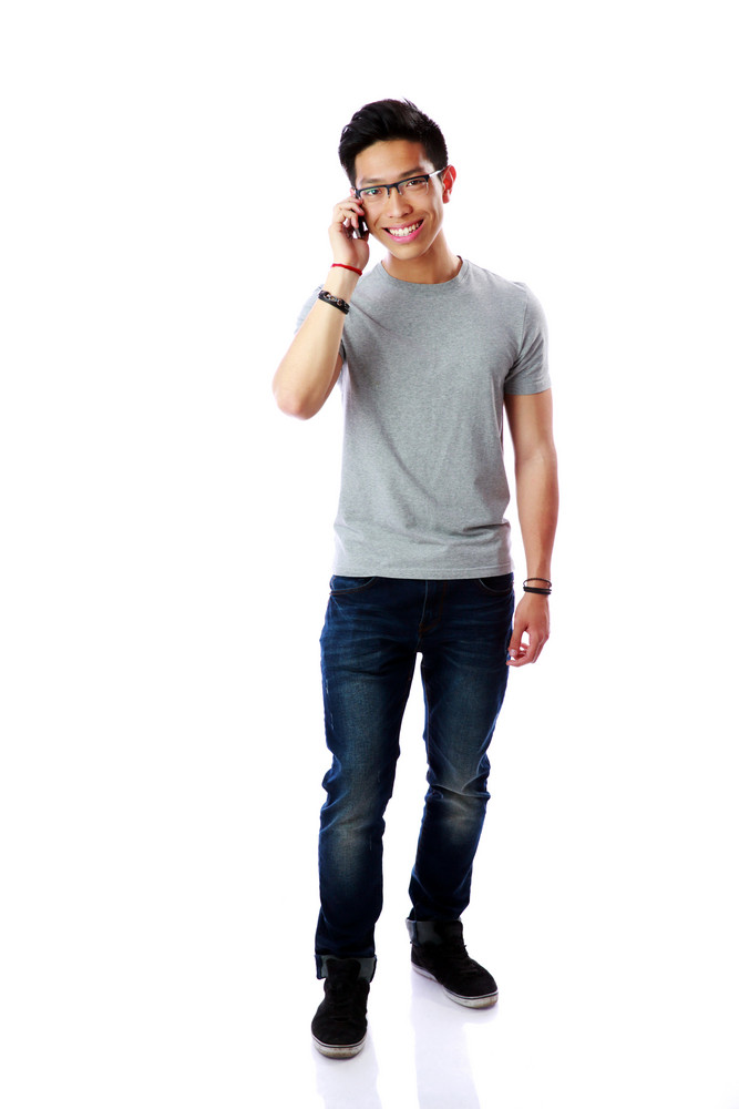 Young cheerful asian man talking on the phone over white background