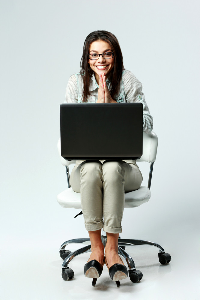Young cheerful businesswoman with laptop sitting on chair on gray background