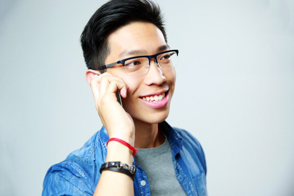 Young cheerful man talking on the phone over gray background