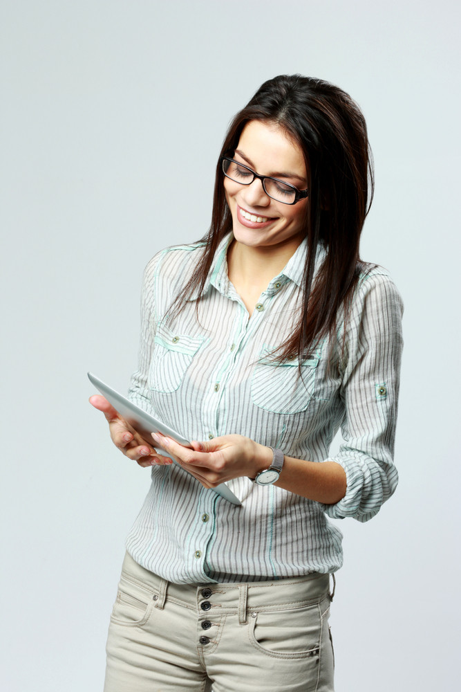 Young cheerful woman using tablet computer on gray background