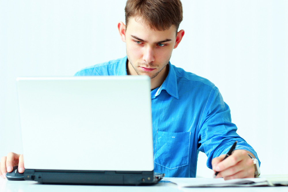Young concentrated businessman writing notes down and looking at laptop in office