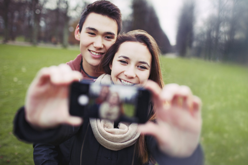 Young couple looking happy while taking pictures using a smart phone at the park. Teenage boy and girl in love photographing themselves outdoors.