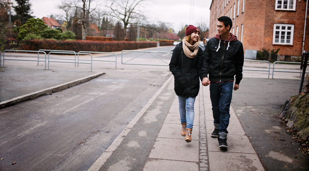 Young couple walking on a sidewalk holding hands looking at each other on a winter day. Asian teenage man and woman walking by a street.