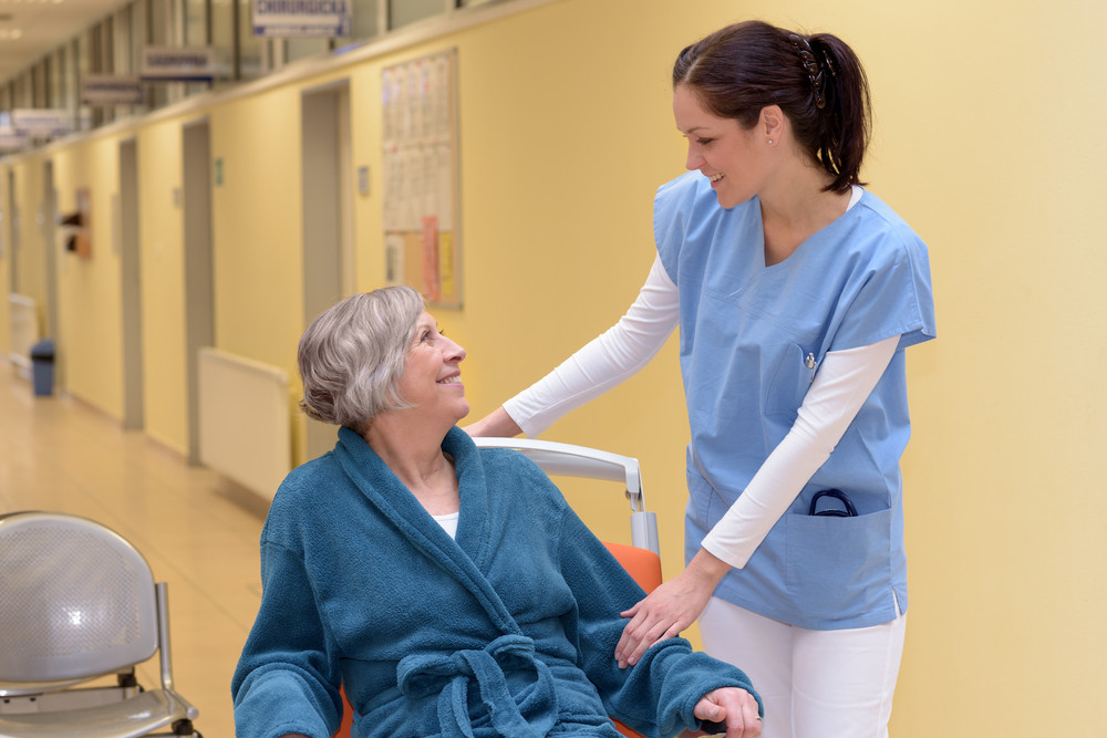 Young female nurse in hospital smiling at senior patient in wheelchair at hospital