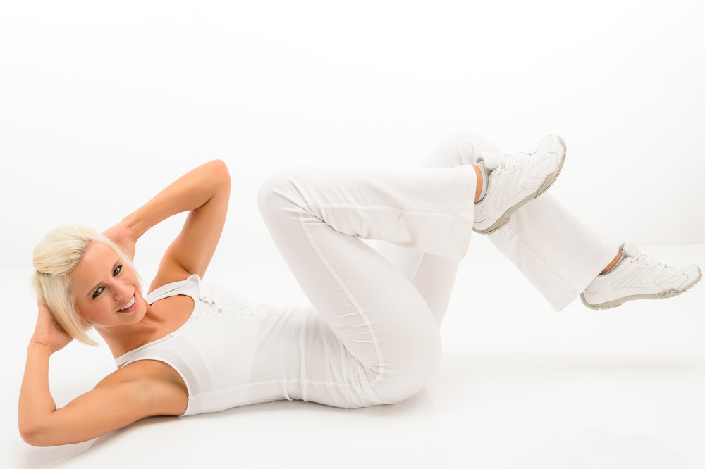 Young Fitness Woman Exercise Abs Lying On White Floor