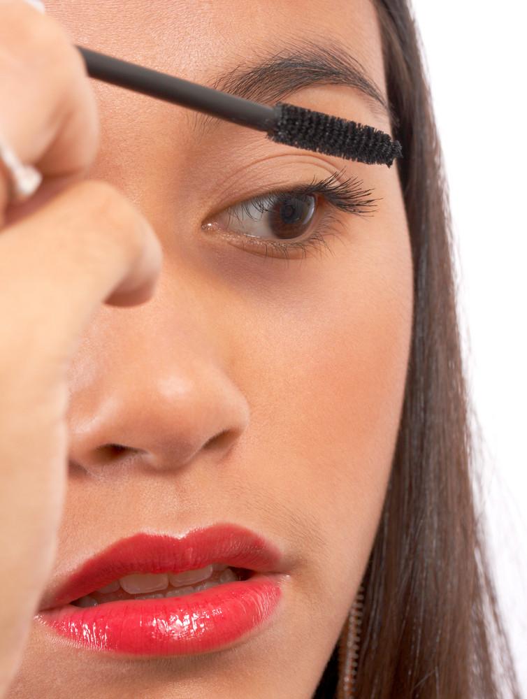 Young Girl Applying Mascara To Eyelashes