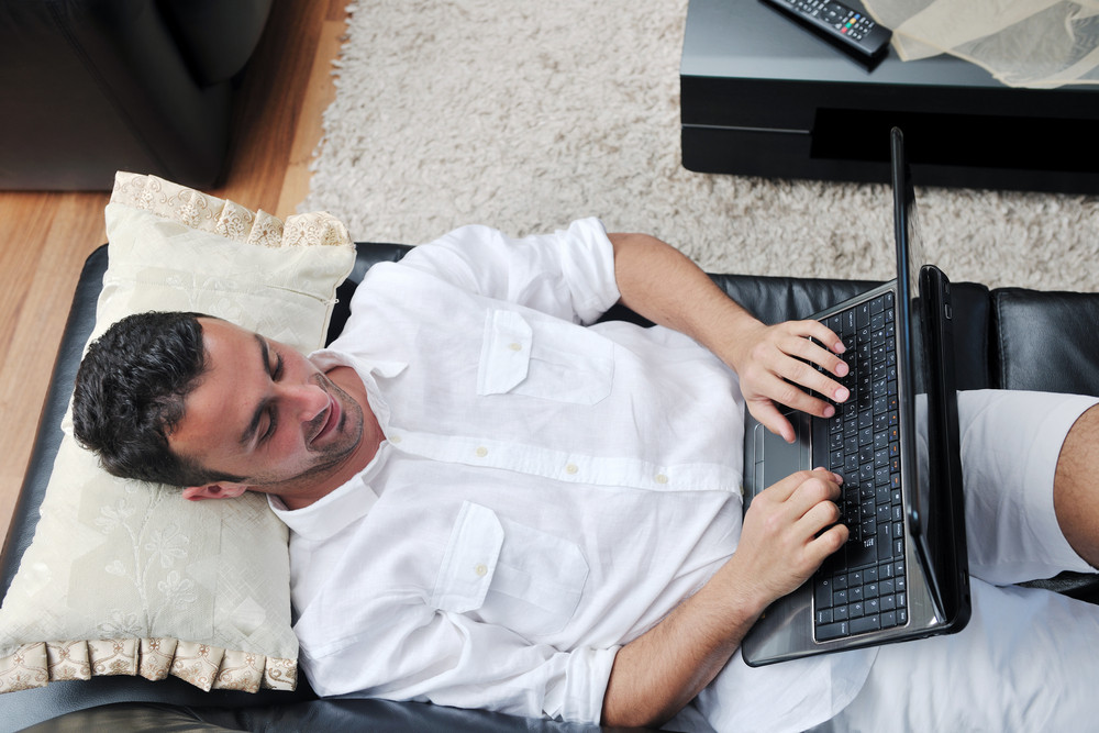 Young guy using laptop at home