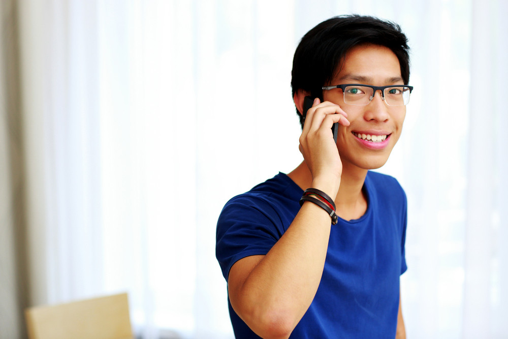 Young happy Asian man talking on the phone