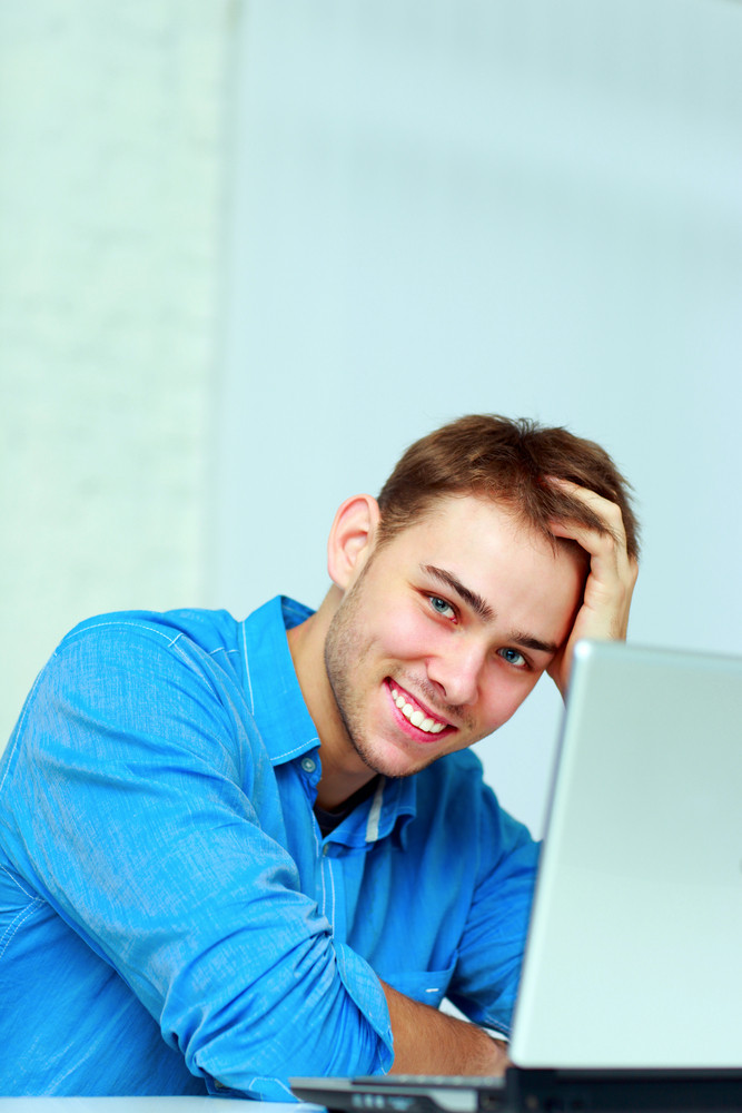 Young happy businessman sitting at the table with laptop in office