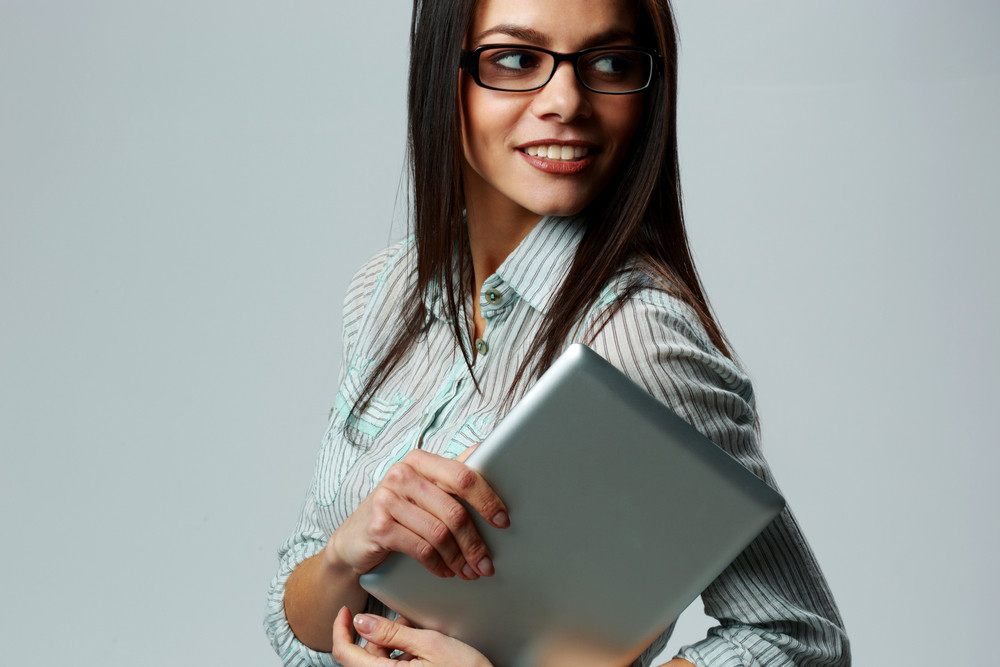 Young happy businesswoman holding tablet computer and looking away on gray background