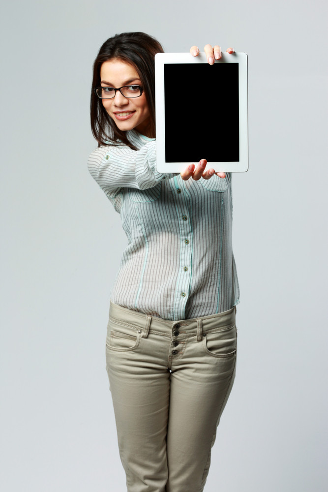 Young happy businesswoman showing tablet computer screen on gray background