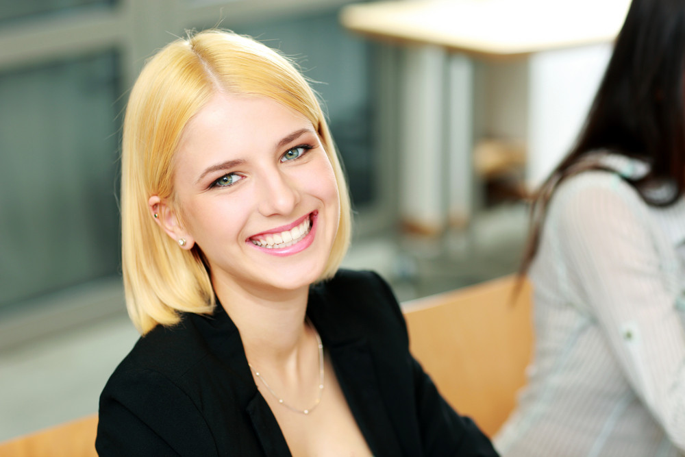 Young happy businesswoman sitting at office