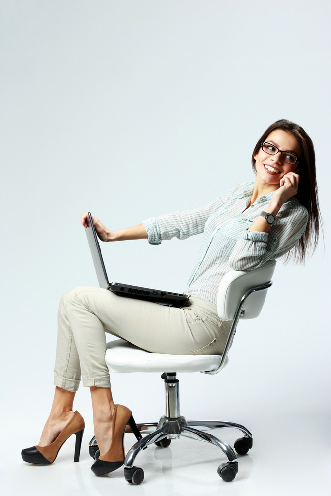 Young happy businesswoman sitting on the chair with laptop and talking on the phone on gray background