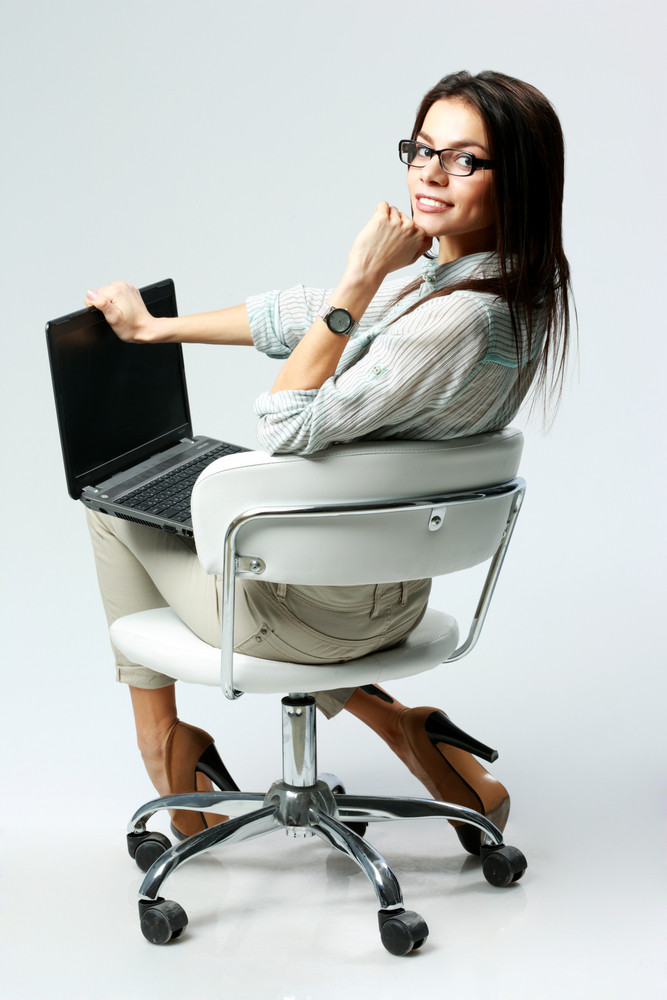 Young happy businesswoman sitting on the office chair with laptop on gray background